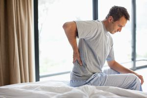 Man sitting on bed with a chronic backache