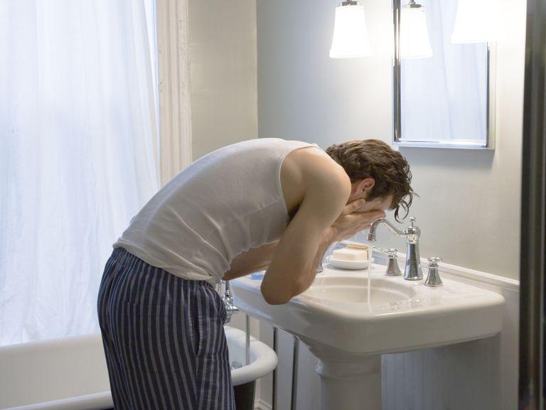 Man washing face in sink, daytime