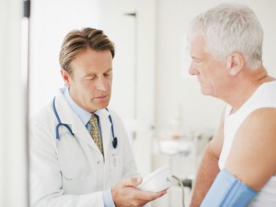 Doctor taking patients blood pressure in doctors office