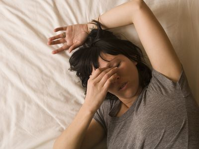 woman laying down with headache