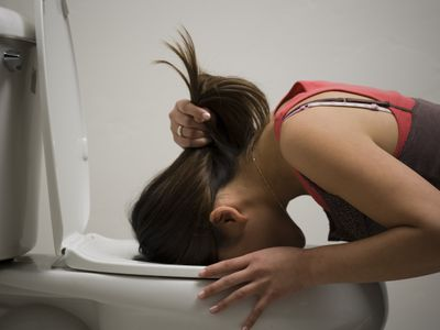 Profile of a young woman vomiting into a toilet bowl