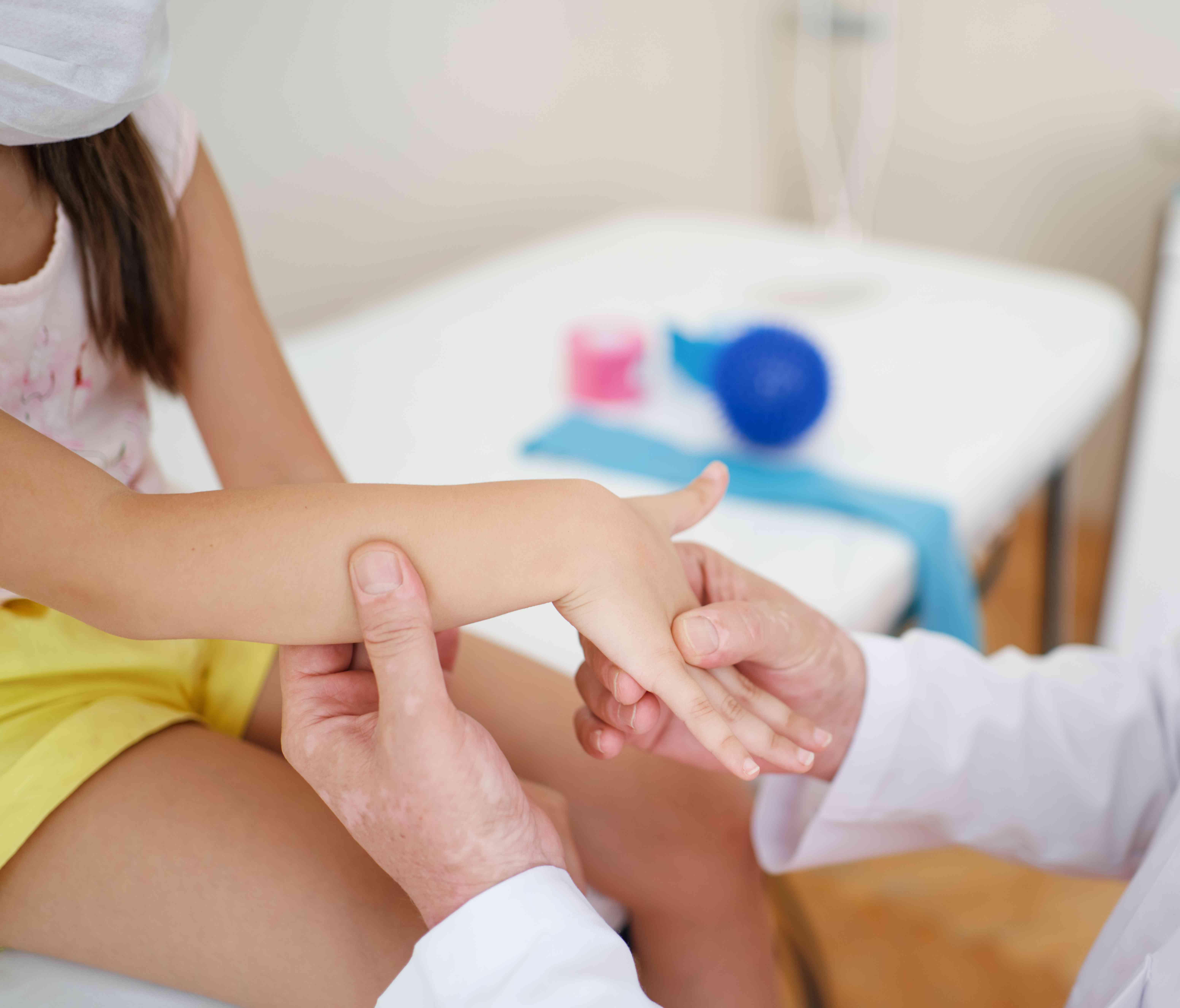 Wrist massage. A male massage therapist puts pressure on a sensitive point on a kid's hand.