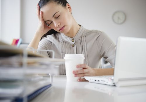 Stressed tired woman at office desk