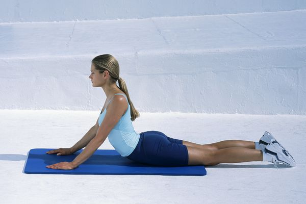 Woman in tank top and shorts performing stretching exercise on exercise mat, hands on mat and back arched