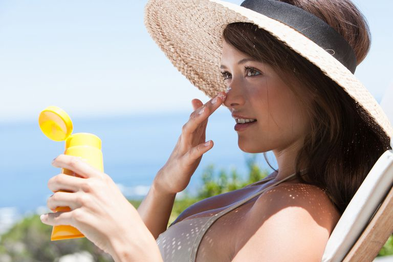 Woman with straw hat applying sunblock to face outdoors