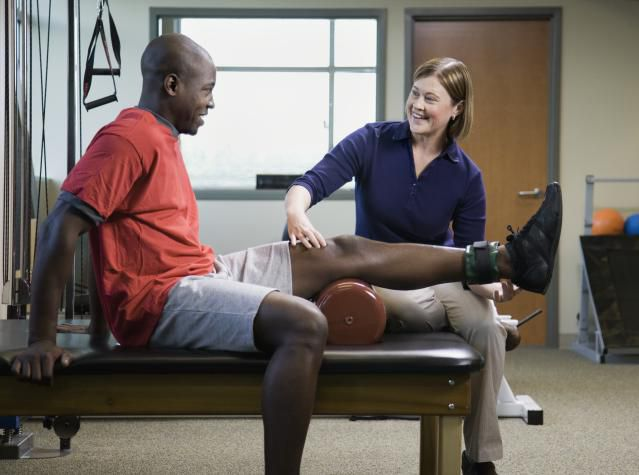 Physical therapy session with PT touching patient's knee