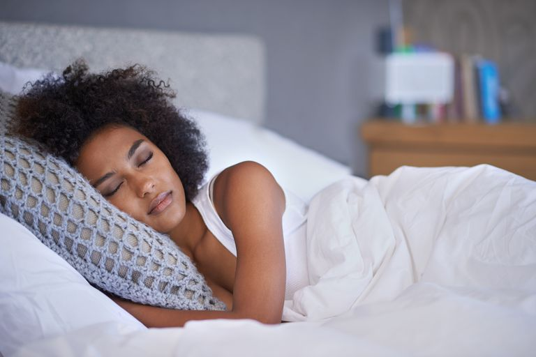 Woman sleeping to meet her sleep needs, feel rested, and avoid the effects of sleep deprivation