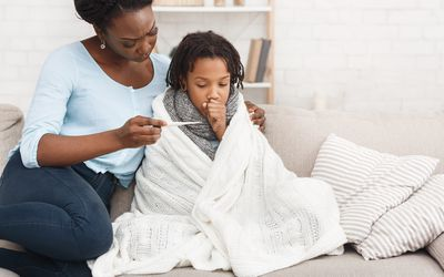 Mother measuring temperature of her sick daughter with thermometer