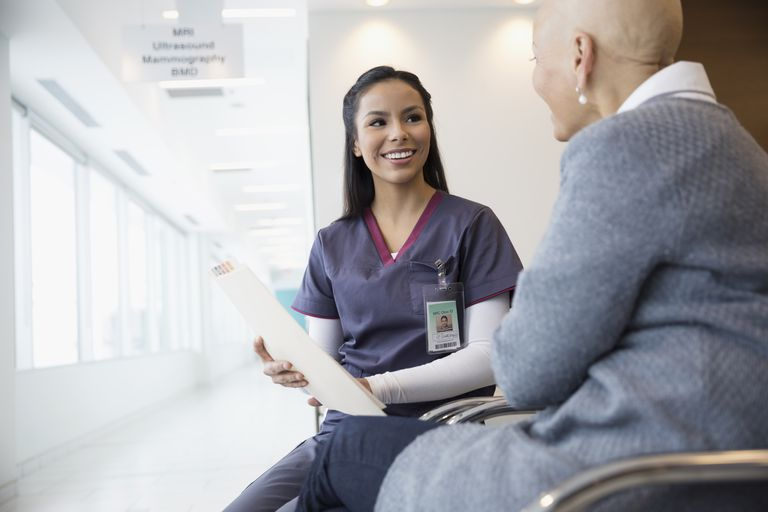 Nurse discussing medical chart with patient in waiting room