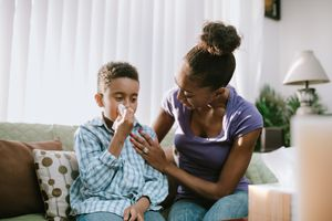 Mother Comforts Sick Child With Cold