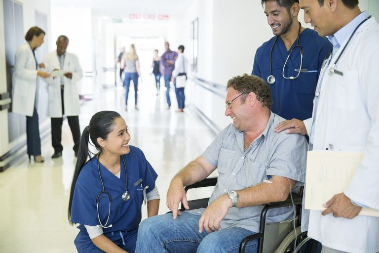 doctors and nurses converse with a male patient