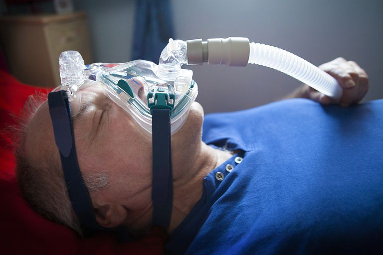Man wearing CPAP mask in bed that may be attached to CPAP, BiPAP (or bilevel), or ASV therapy for sleep apnea