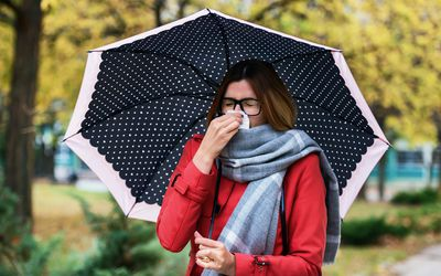 A woman holding a polka dot umbrella is holding a tissue to her nose.