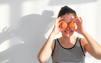 Portrait of a woman in a black and white striped tank top standing against a white wall, off to the left side of the frame. She is holding two eggs up in front of her eyes.