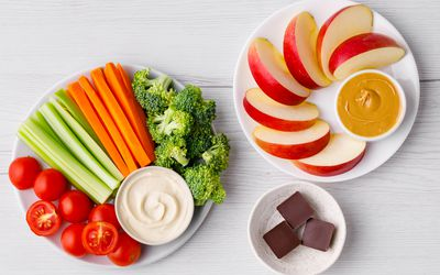 Plate of veggies, dark chocolate and apples with peanut butter