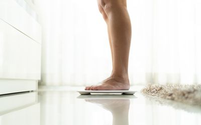 Low Section Of Woman Standing On Electronic Weight Scale On Floor