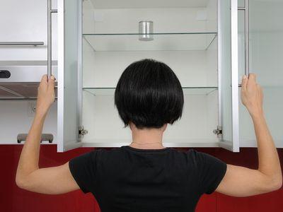 A woman looks inside an empty cupboard.