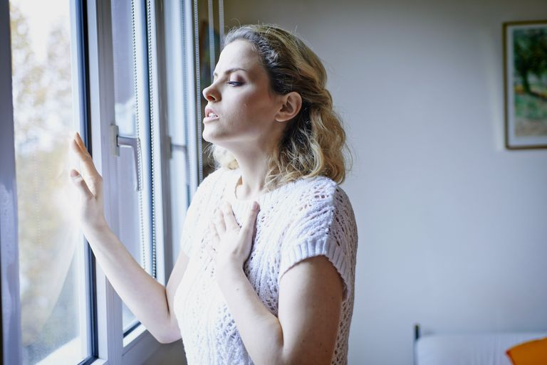 Woman with breathing difficulties looking out a window