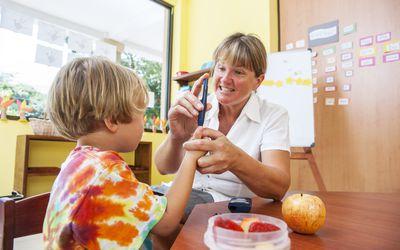 School nurse checks child's blood sugar in office