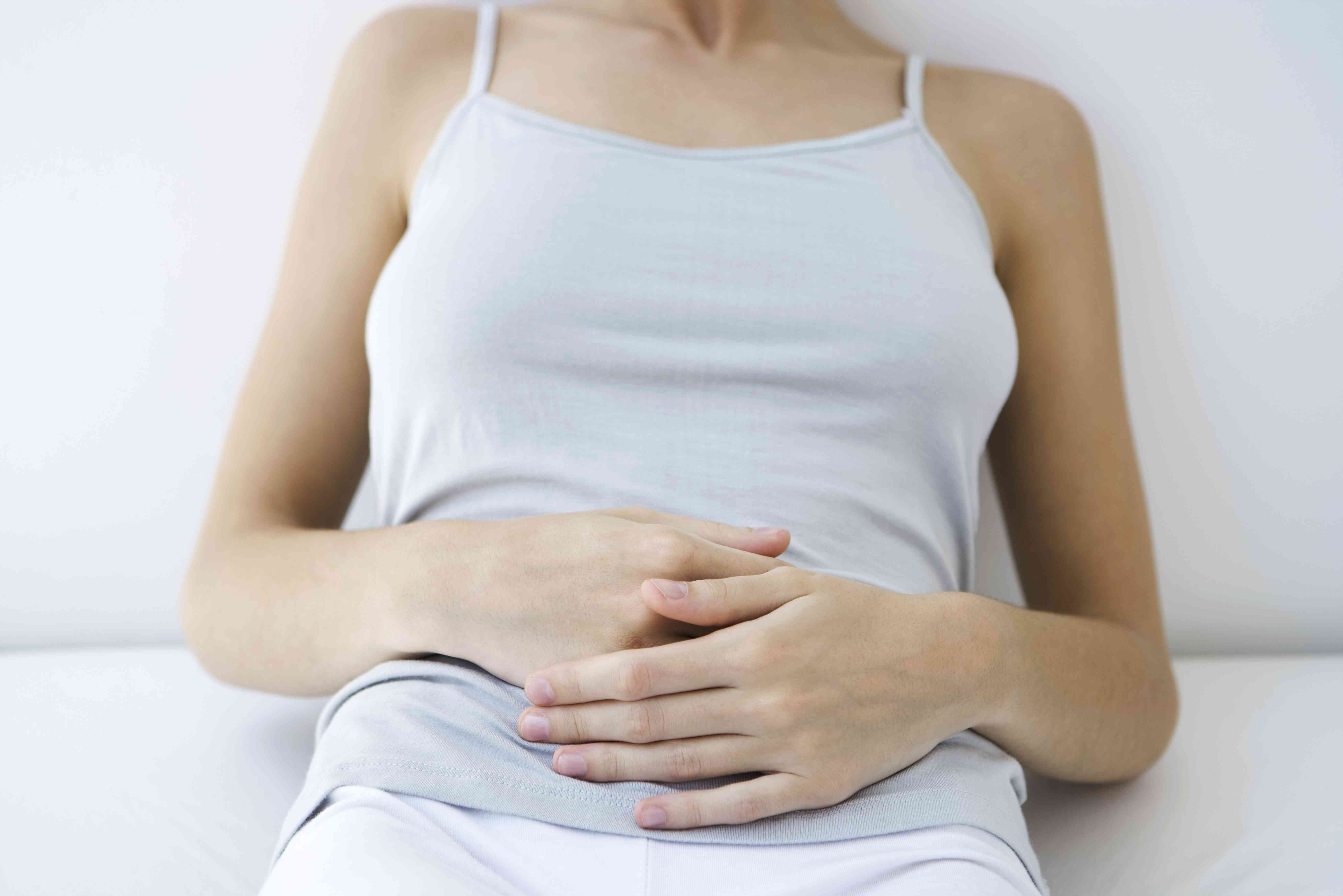 Woman holding stomach in discomfort