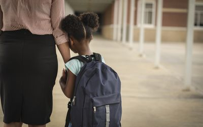 Elementary age, Black girl holds mom or teacher's hand before school begins. She wears a backpack and clings to mom with uncertainty about starting school.