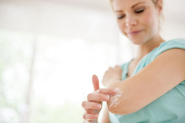 Woman applying cream to elbow