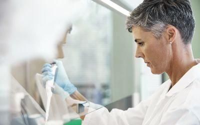 Scientist conducting cancer research in laboratory - stock photo