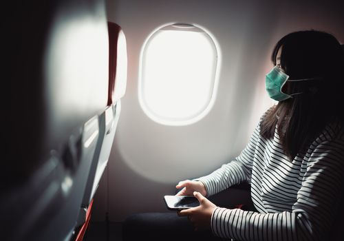 Young woman on plane wearing face mask.