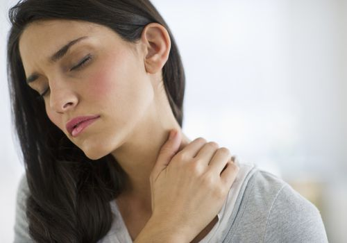 Woman in pain rubbing her neck
