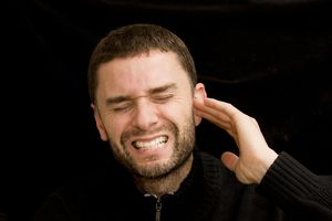 young man with a beard holding his ear and cringing in pain