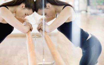 Woman leaning on a ballet bar