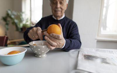Man cutting an orange