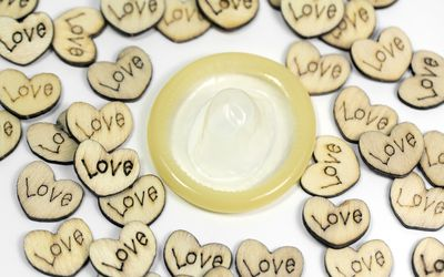 A rolled up condom surrounded by wooden hearts carved with the word
