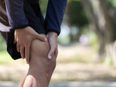 man holding hurt knee while standing