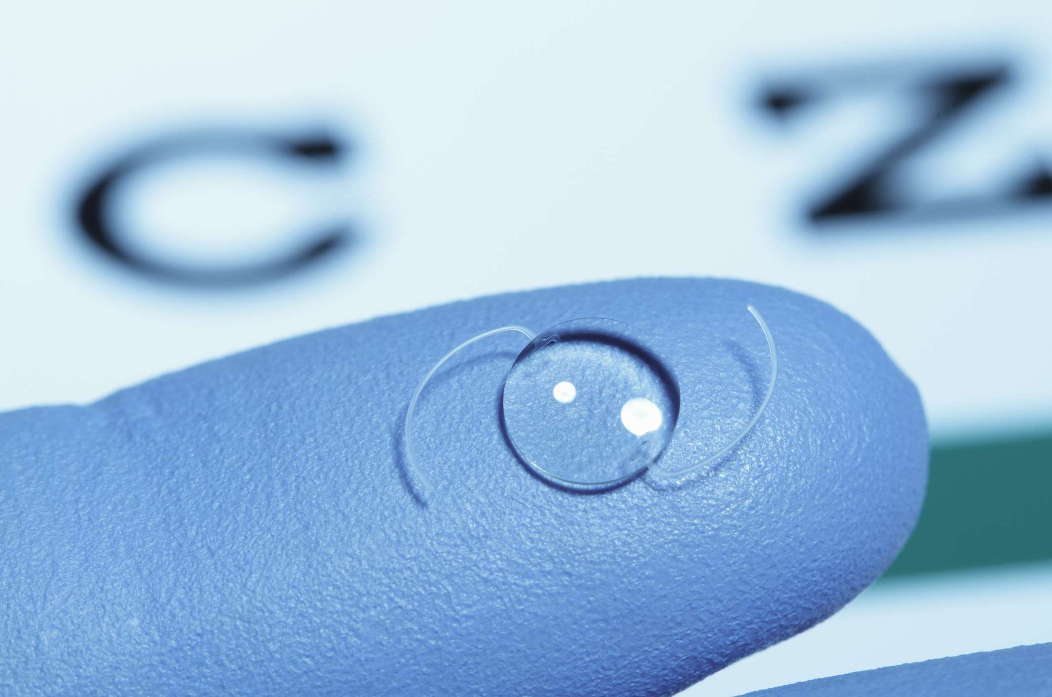 Intraocular (artificial) lens on gloved finger.
