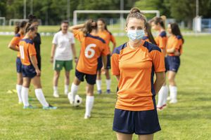 Young white woman in a soccer uniform wearing a face mask; her teammates are blurred in the background.