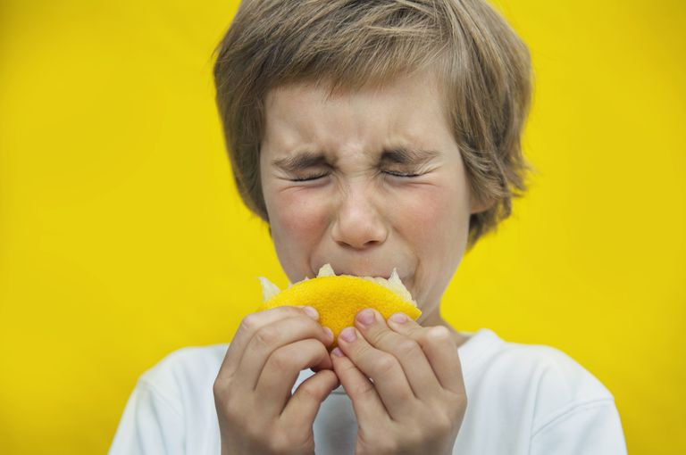 Child sucking on a lemon