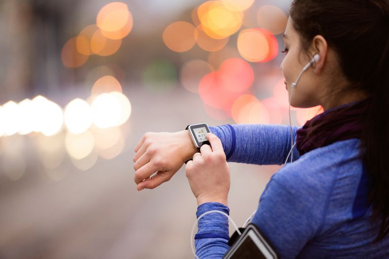 woman checking smartwatch on run