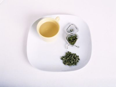 brewed green tea in a mug and dried green tea on a plate