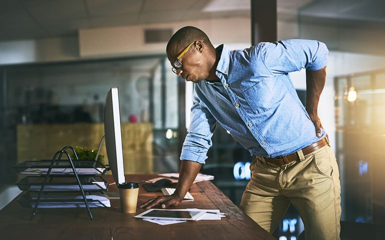 Man standing at his desk holding his back in pain