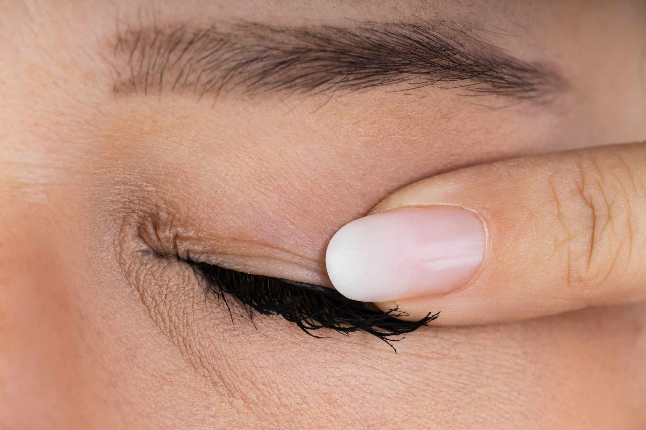 Finger pressing on a closed eyelid near the lashes