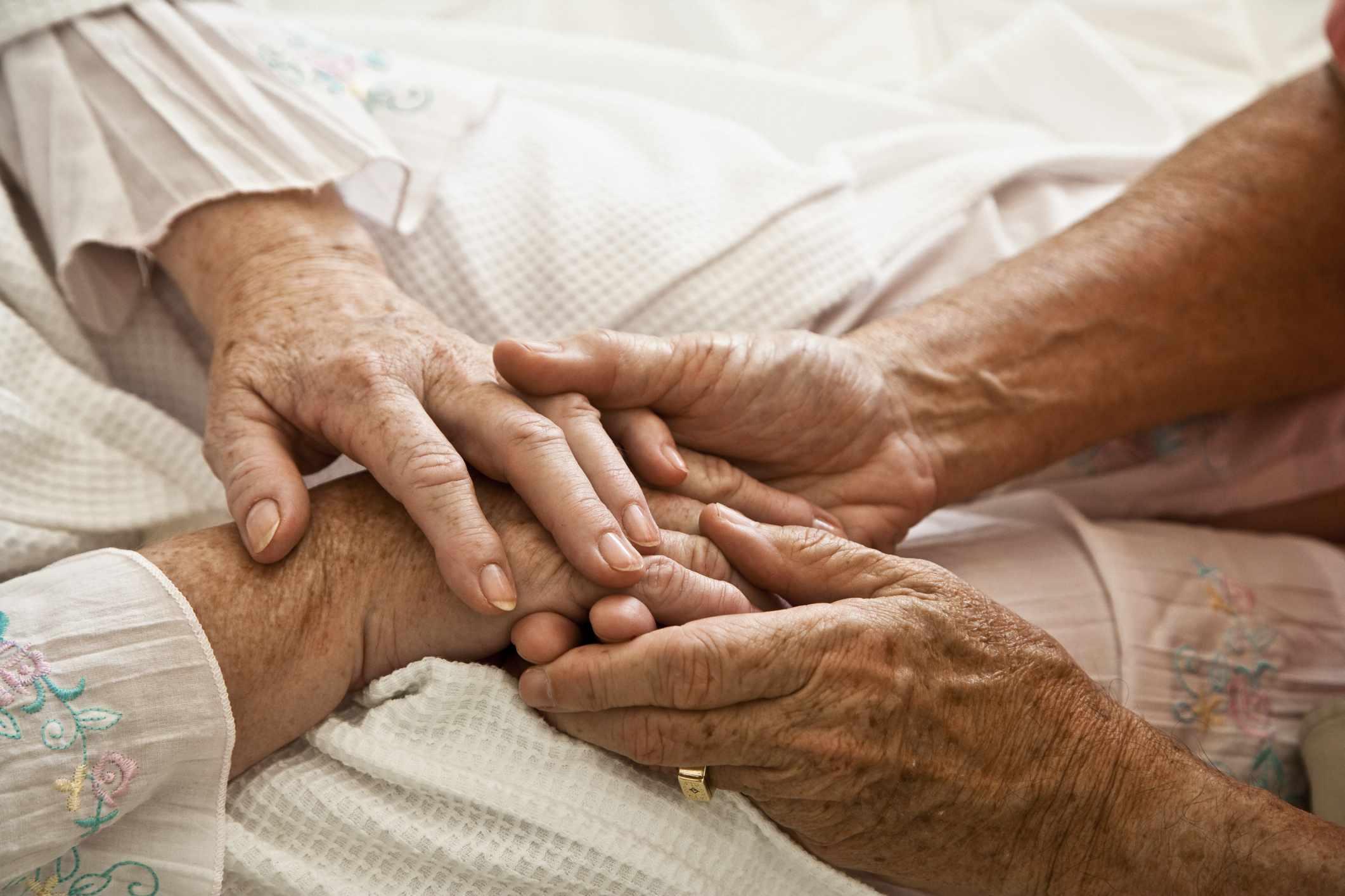Close up of older two older people holding hands
