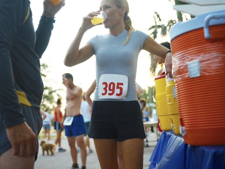 Woman running race, stopping to drink at an aide station