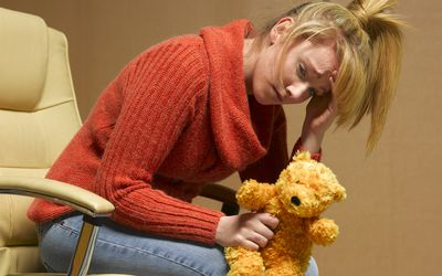 A young white woman sits in a chair, resting her head on her hand, and holding a teddy bear.