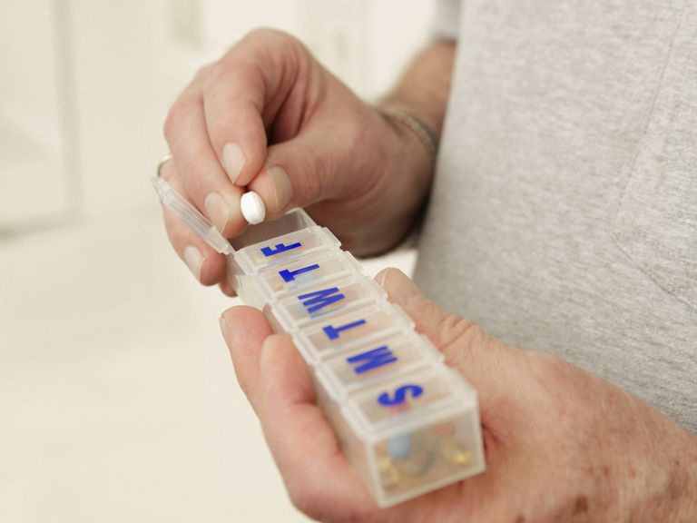 person taking pill out of pill case