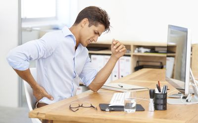 a man holding his back sitting at a desk
