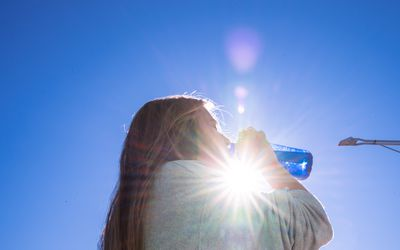 Woman drinking water is illuminated by the sun behind her