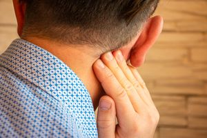 Pain behind ear in area of mastoid process concept photo. Person holds his hand over area behind ear, where pain is suspected due to otitis media, inflammation, noise in ear, hearing loss