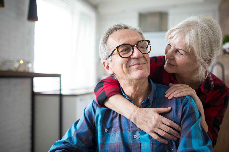 Happy senior woman embracing her husband