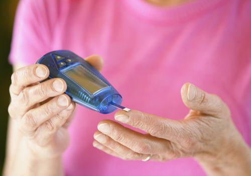 woman testing blood sugar with meter